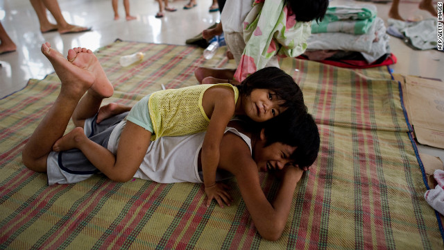 Children play at an evacuation center at a municipal building Friday in the township of Paombong on the outskirts of Manila.