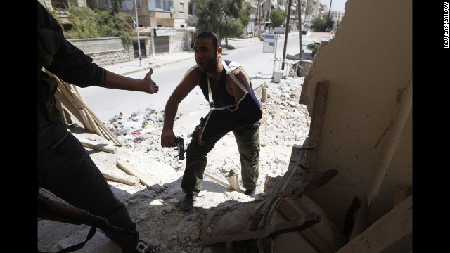 Free Syrian Army fighters walk through a damaged building during heavy fighting in the Salaheddine neighborhood.