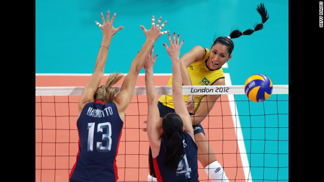 No. 8 Jaqueline Carvalho of Brazil spikes the ball against the United States' No. 13 Christa Harmotto and No. 4 Lindsey Berg during the women's volleyball gold medal match.