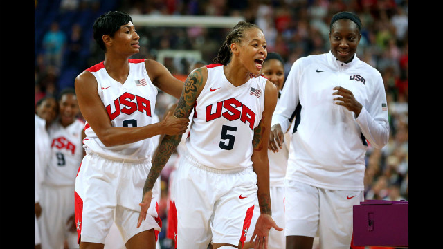 Seimone Augustus, number 5, and Angel McCaughtry, number 8, celebrate with the rest of the U.S. women's basketball team after defeating France 86-50 to win the gold medal.