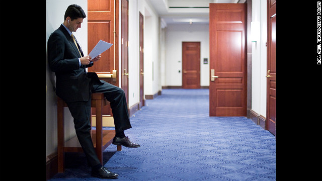 Ryan looks over papers as he waits for other House Republicans to arrive for a news conference in the Capitol Visitors Center.