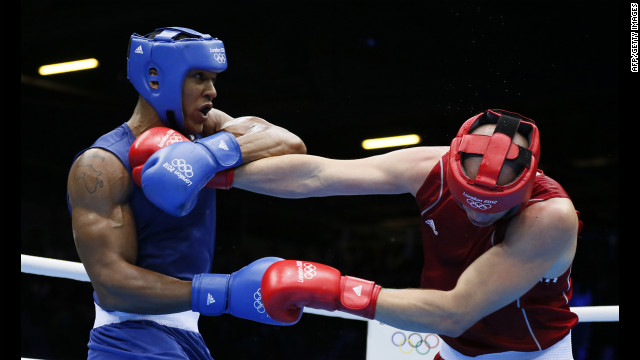 Ivan Dychko of Kazakhstan, in red, defends against Anthony Joshua of Great Britain, in blue, during the men's super-heavyweight (+91 kilogram) boxing semifinals.