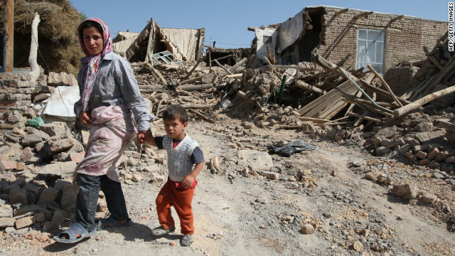 Residents walk among the rubble of destroyed buildings in the village of Amir-Ali Kandi.