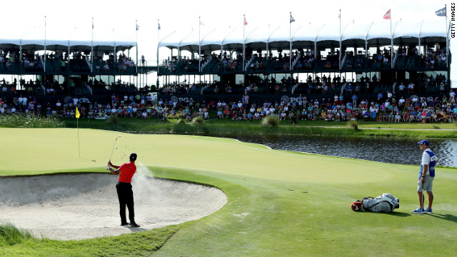 Tiger Woods hits out of the sand on the 17th hole during the third round.