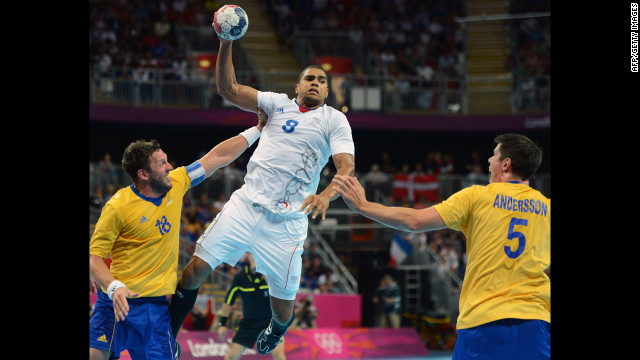France's centerback Daniel Narcisse, center, is challenged by pivot Tobias Karlsson, left, and right back Kim Andersson of Sweden during the men's gold medal handball match between Sweden and France.