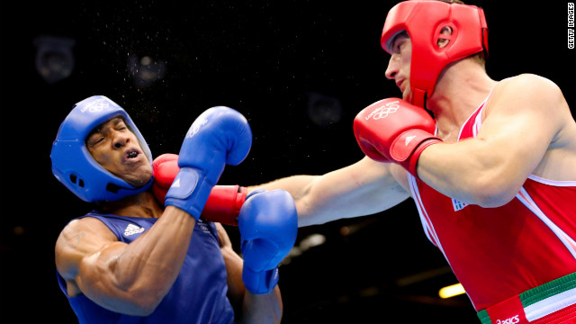 Sweat flies off Anthony Joshua of Great Britain as he takes a punch from Roberto Cammarelle of Italy during the men's super heavyweight boxing final bout. Joshua went on to win the gold medal.