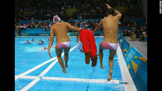 Two Croatian players and a member of the coaching staff jump into the pool after winning the gold medal in men's water polo.