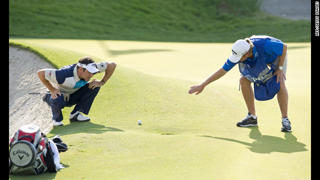 Trevor Immelman of South Africa and his caddy examine the green before a putt.