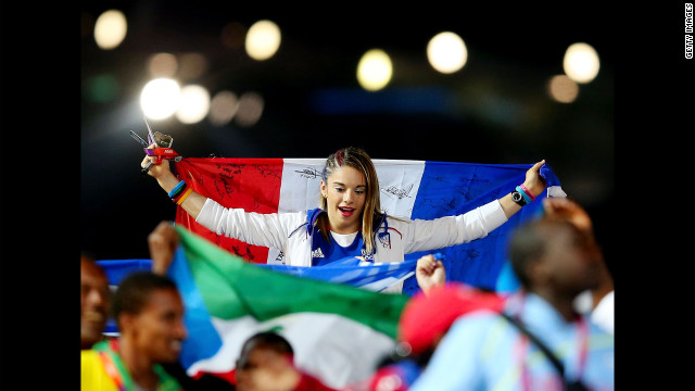 A French athlete carries her nation's flag as the French team parades through the stadium.