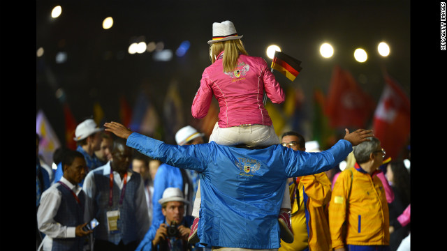 A female athlete from Germany rides on the shoulders of a male teammate during the closing ceremony.