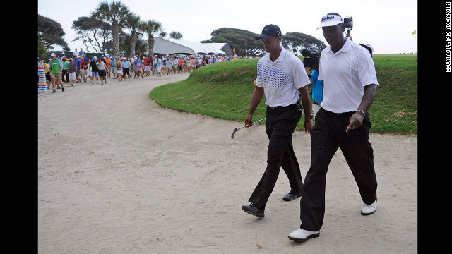 Tiger Woods, left, and Vijay Singh of Fiji walk off the course after the suspension of play.