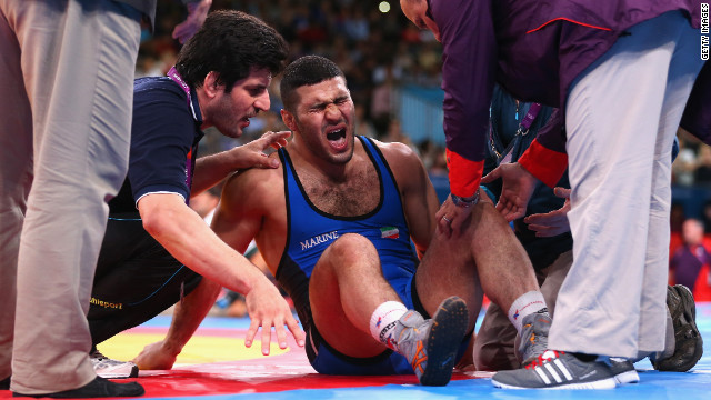 Reza Mohammad Ali Yazdani of Iran is treated for an injury during the men's freestyle wrestling 96-kilogram semifinal match.