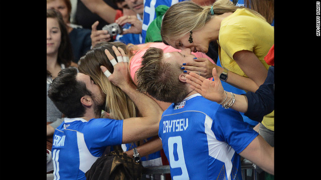 Italy's Michal Lasko, left, and Ivan Zaytsev seal their victory with a kiss from loved ones after defeating Bulgaria in the men's volleyball bronze medal match.