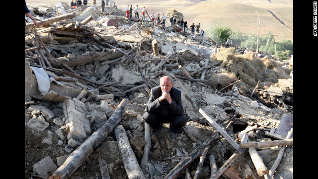 An Iranian resident from the village of Baje-Baj, near the town of Varzaqan, stands on top of the rubble of his destroyed home.
