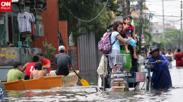 iReporter Reynaldo Cedilla captured this image of the heavy flooding in Manila, Philippines. &quot;Underpasses were not passable to any type of vehicles due to the high water level. In the streets there were waist and knee deep floodwaters. ... Stranded locals tried to wade through it despite the danger,&quot; he said.