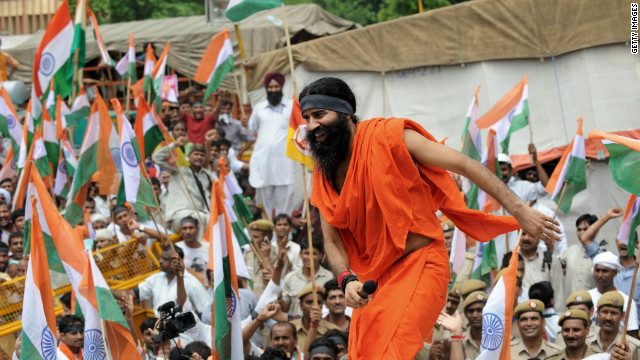 Indian yoga guru Baba Ramdev climbs onto the roof of a car to address his followers in New Delhi on Tuesday.