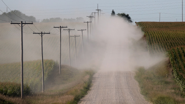 A car kicks up dust as it drives by corn fields on dry dirt road in State Center, Iowa.