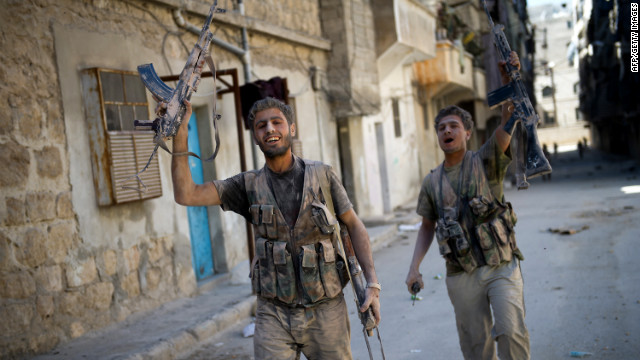 Rebels covered in dust and debris emerge from a building hit by an army tank shell Monday in Aleppo's Salaheddin area.