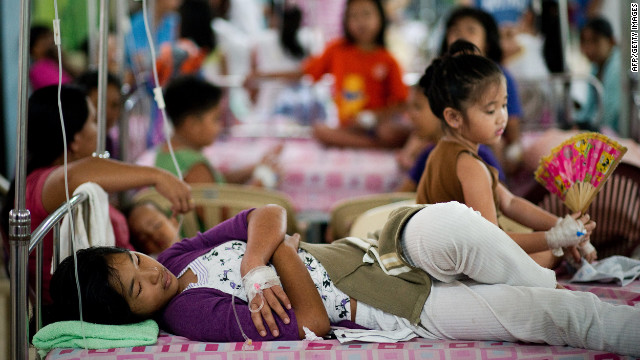 People with dengue fever rest Tuesday at a hospital in Manila.