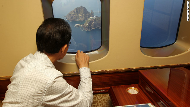 South Korean President Lee Myung-Bak points through the window of a helicopter at the remote islands disputed with Japan on August 10, 2012. It was the first visit by a South Korean president to the islands, which prompted Tokyo to recall its ambassador from Seoul in protest.