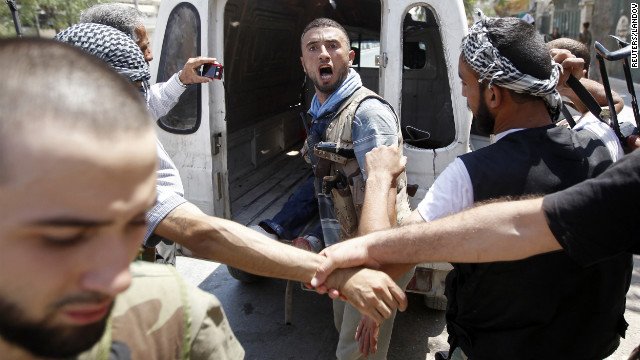 A Free Syrian Army fighter learns that his commander has been killed by a tank shell in Aleppo on Tuesday, August 14. Opposition activists say shelling in dissident strongholds has exacerbated the humanitarian crisis in<br /> 1000<br />  the country.