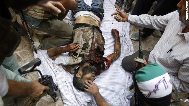 Free Syrian Army fighters look at the body of their commander killed by a tank shell Tuesday in Aleppo.