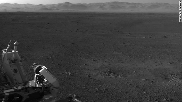 This image, with a portion of the rover in the corner, shows the wall of Gale Crater running across the horizon at the top of the image. 