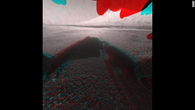 "This image is a 3-D view in front of NASA's Curiosity rover. The anaglyph was made from a stereo pair of Hazard-Avoidance Cameras on the front of the rover. Mount Sharp, a peak that is about 3.4 miles high, is visible rising above the terrain, though in one ""eye"" a box on the rover holding the drill bits obscures the view."