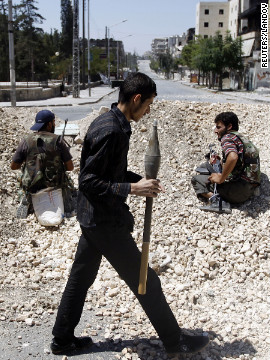 Rebel fighters sit behind a barricade of rocks on an Aleppo street.