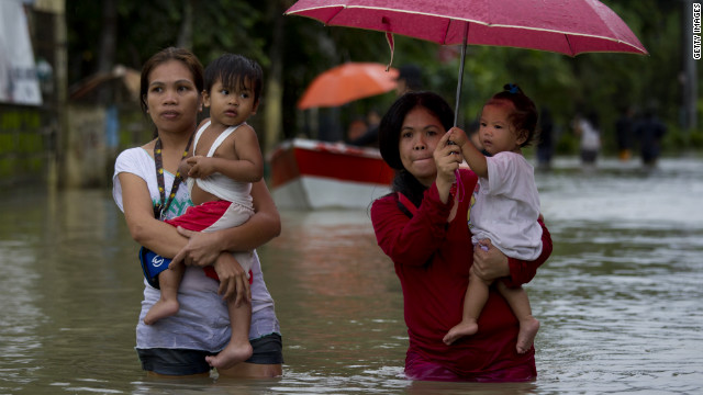 Mothers carry their children through a flooded street.