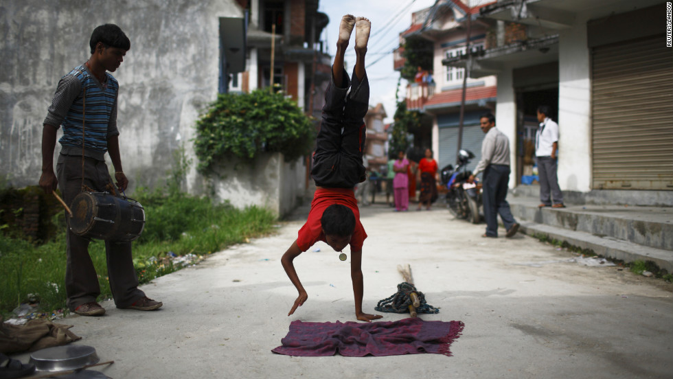Gchan Choudhary, 17, plays a drum as his younger brother Drumpal Choudhary, 11, performs tricks on a Kathmandu, Nepal, street on Wednesday. The Indian immigrants say they earn about $10 a day.