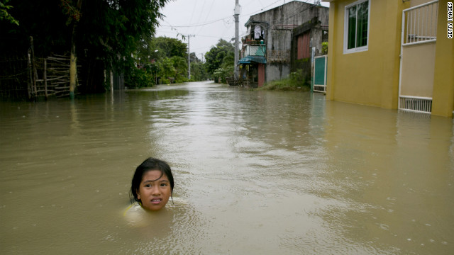  A girl is submerged in the water outside her home next to the swollen Pampanga River on Wednesday, August 15, in Bulacan, Philippines. 