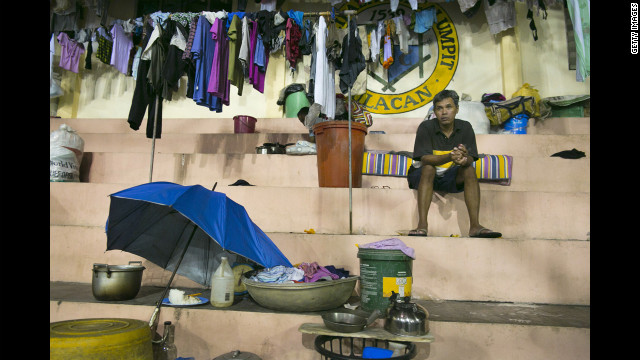 A flood victim sits at a crowded evacuation center in a neighborhood covered in water in Bulacan.