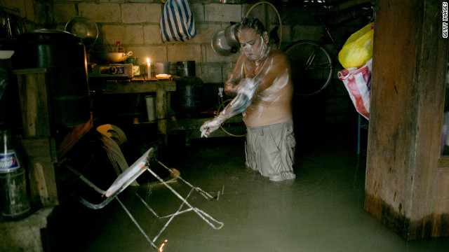 Antonio Navarro Sambiilay bathes inside his flooded home in Bulacan, Philippines.