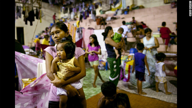 Displaced flood victims pack a crowded evacuation center in a flooded neighborhood.