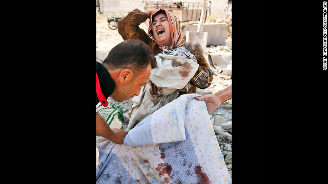 A Syrian woman holds her dead baby as she screams upon seeing her husband's body being covered following an airstrike by regime forces on the town of Azaz on August 15, 2012.