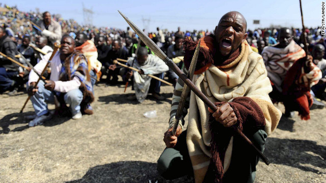 Striking South African miners armed with homemade spears and pangas chant slogans near Marikana platinum mine in Rustenburg, South Africa, on Thursday, August 16. Rising tensions at the mine exploded Thursday in grisly violence as police opened fire on striking miners.