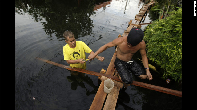 Filipino residents reinforce a footbridge on a flooded road. Last week's deluge was the worst to hit Manila and surrounding areas since 2009, when Tropical Storm Ketsana caused flash floods that left hundreds dead or missing.