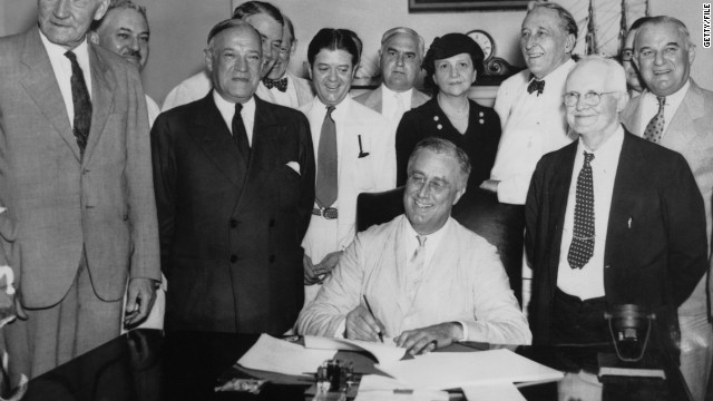 Franklin Roosevelt signs the 1935 Social Security Act into law.