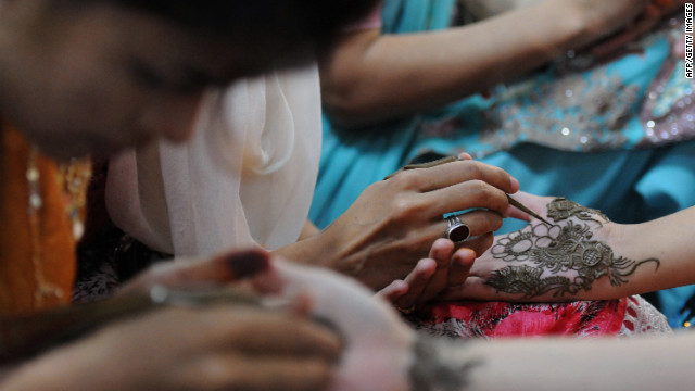 Beauticians apply traditional henna designs to the hands of customers ahead of the Muslim festivities of Eid al-Fitr in Karachi.<br/><br/>