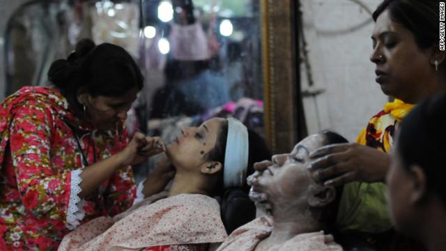 Pakistani beauticians attend to their customers ahead of the Muslim festivities of Eid al-Fitr, in Karachi.