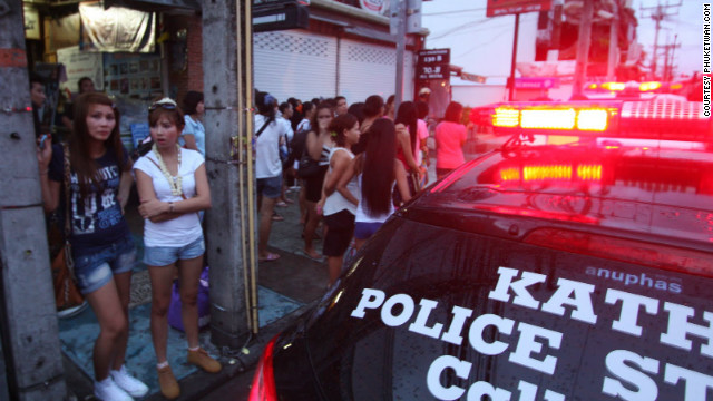 Club goers stand in the street as police attend the scene of the fire. Eleven others were injured when flames engulfed the Tiger Bar in Patong.<br/><br/>Photo courtesy of <a href='http://phuketwan.com/' target='_blank'>Phuketwan.com</a>