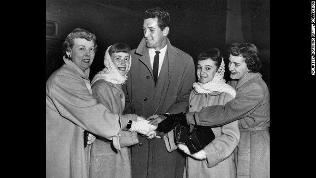 Rock Hudson cuddles with fans at Midway airport.