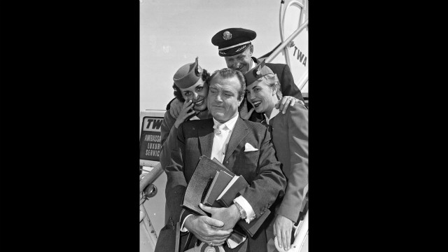 Comic Red Skelton poses with TWA flight crew and pilot in the 1950s.