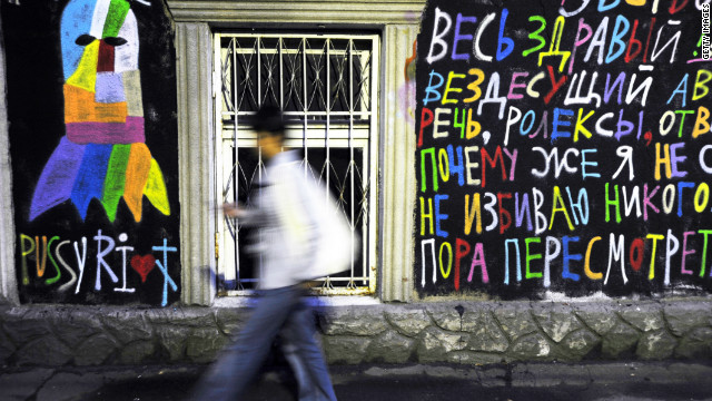 "A man walks past pro-Pussy Riot graffiti in Moscow. Band members were charged after screaming ""Mother Mary please drive Putin away"" during a concert inside Christ Savior Cathedral, in February."