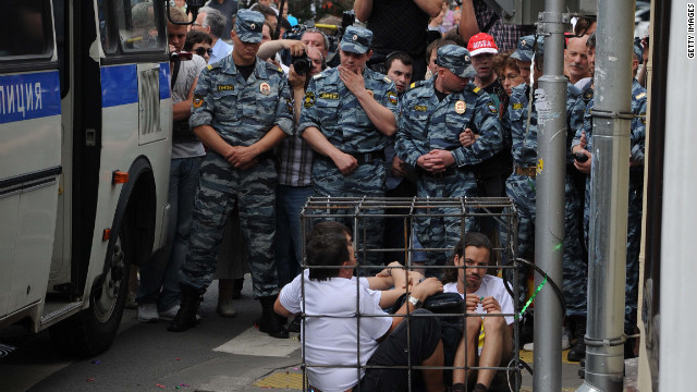 "Supporters sit locked in a mock defendants cage outside a Moscow court. The band members have been charged with hooliganism aimed at ""inciting religious hatred."""