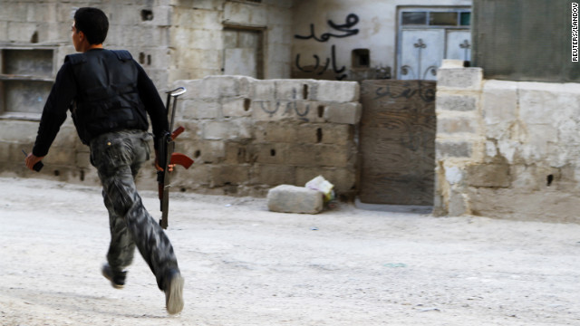 A fighter with the rebel Free Syrian Army secures a street Friday in the Damascus suburb of Saqba. Fighting raged unabated Friday across Syria, while diplomats struggled to find a political solution.