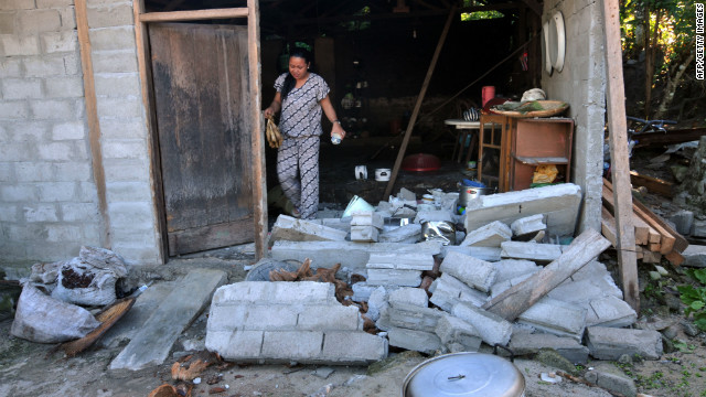 A woman checks her damaged house in the village of Tuva village on the eastern Indonesian island of Sulawesi on August 19, 2012 following the earthquake.