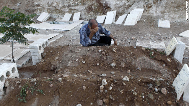 A man cries near the graves of his two children killed during a recent Syrian airstrike in Azaz on August 20.