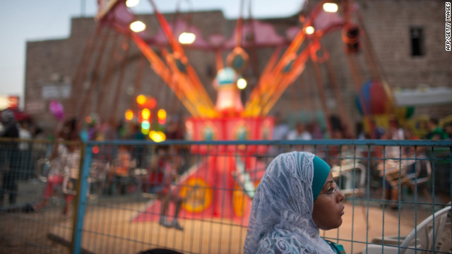 An Israeli Arab woman looks on at an amusement park as Muslims celebrate the Eid al-Fitr holiday Monday in the old city of Acre, Israel.